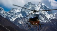 A helicopter flies by the mountain with snowy peaks.